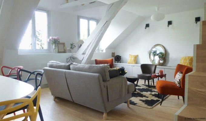 choisy paris pratique fonctionnel design contemporain tendance salon poutre escalier bois parquet canapé gris fauteuil orange Kartell