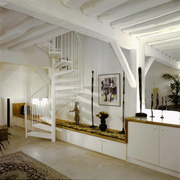 gaité paris appartement rénovation volume duplex triplex escalier monumentale métal blanc tout étage poutre apparente blanche peinte meuble sur mesure blanc bois carrelage beige banc statuette déco africaine coloniale
