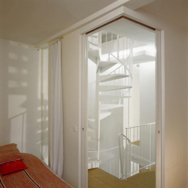 gaité paris appartement rénovation volume duplex triplex escalier monumentale métal blanc tout étage poutre apparente blanche peinte meuble sur mesure blanc bois beige banc