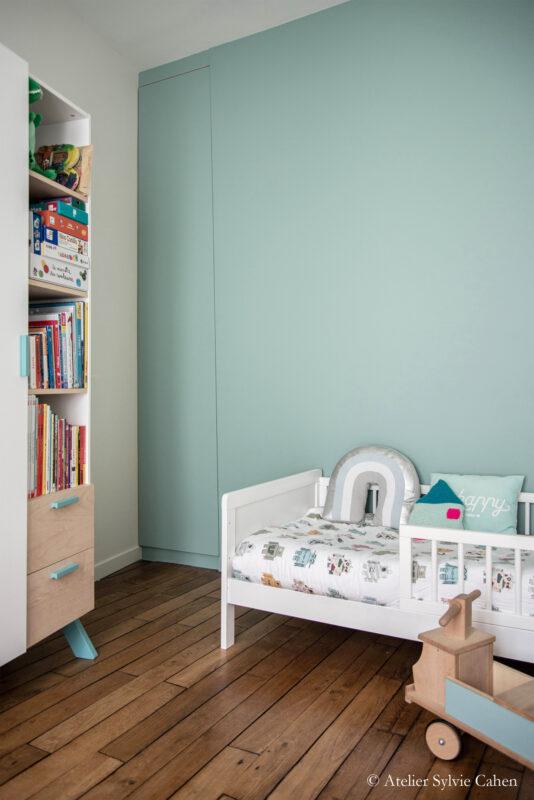 Aménagement de combles. Chambre d'enfant avec mur vert d'eau.