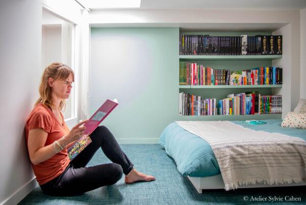 Aménagement de combles. Chambre parentale avec bibliothèque murale. Une femme lit un livre assise sur le sol, adossé au mur de gauche.