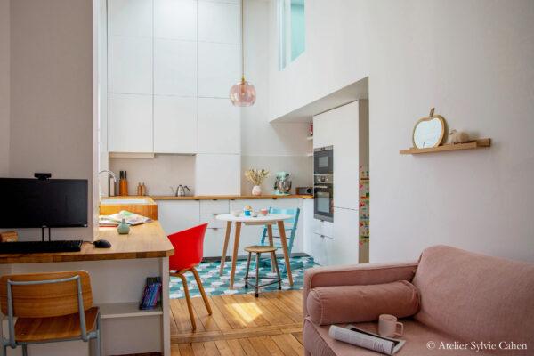 Aménagement de combles. Séjour avec bureau, cuisine, et vue sur la chambre en mezzanine