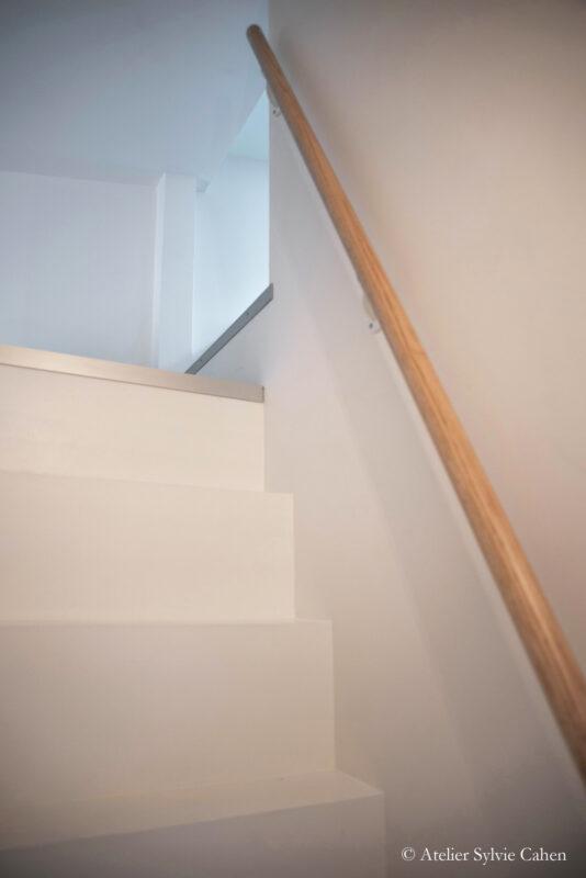 Aménagement de combles. Escalier (blanc) qui monte à l'étage avec rambarde en bois.