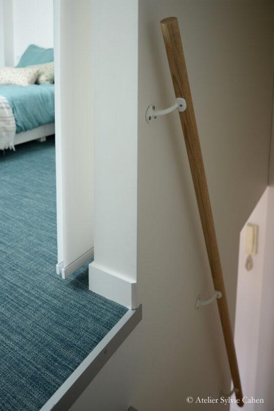 Aménagement de combles. Rambarde d'escalier en bois. avec vue sur la chambre parentale en mezzanine
