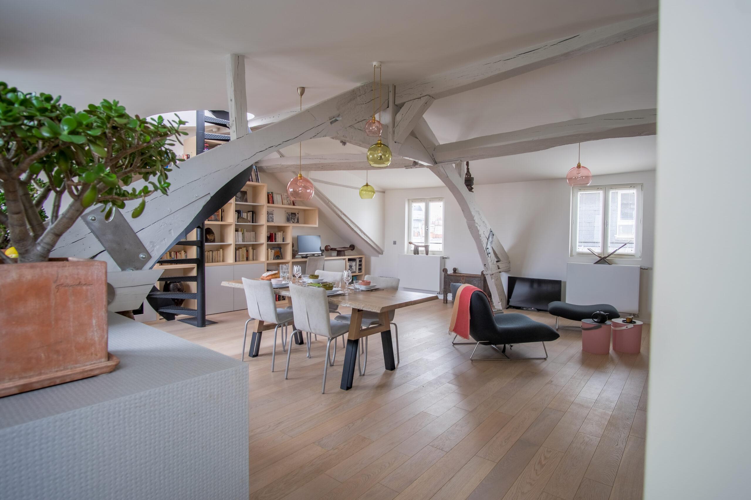 Duplex atypique. Salon / séjour et salle à manger en loft. Avec bibliothèque sur mesure et escalier en colimaçon.