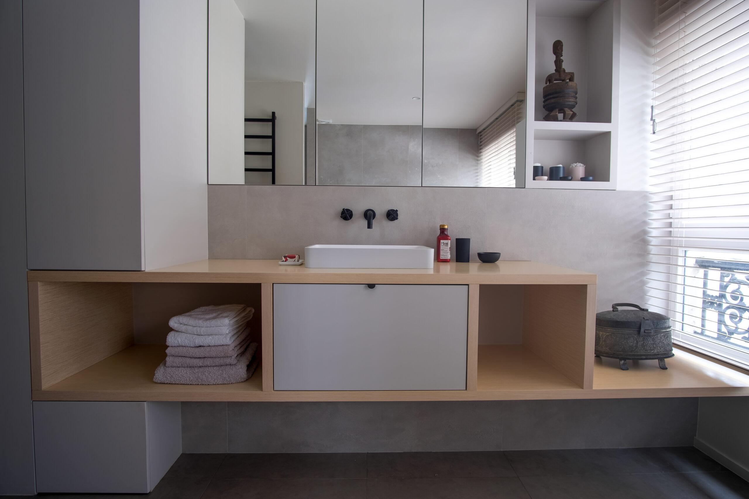 Duplex atypique. Salle de bain avec meuble à vasque posé et meuble à miroirs.