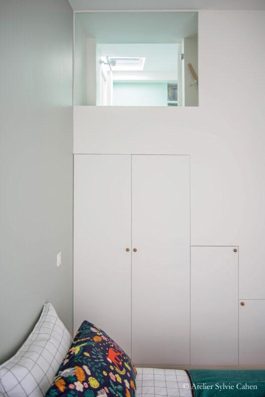 Aménagement de combles. Chambre parentale avec fenêtre en hauteur, donnant sur la chambre enfant, en mezzanine.