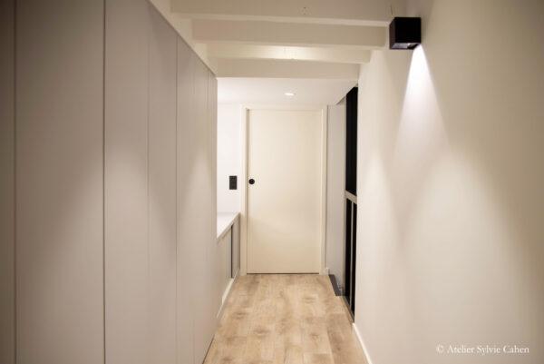 Loft à Lyon. Couloir avec placards et aperçu sur l'escalier descendant sur la droite et la porte de la chambre