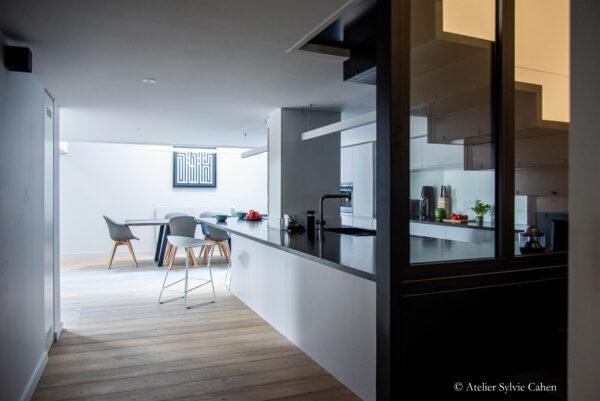 Loft à Lyon. Espace cuisine avec bar et l'escalier montant à l'étage. Vue du dégagement.