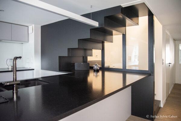 Loft à Lyon. Cuisine et escalier montant à l'étage. Vue du devant du plan de travail.