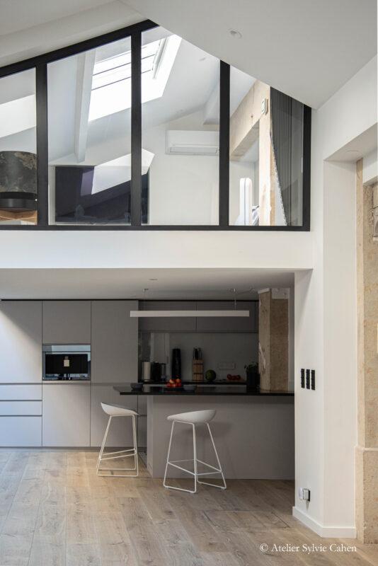 Loft à Lyon. Espace cuisine avec bar et chambre en mezzanine