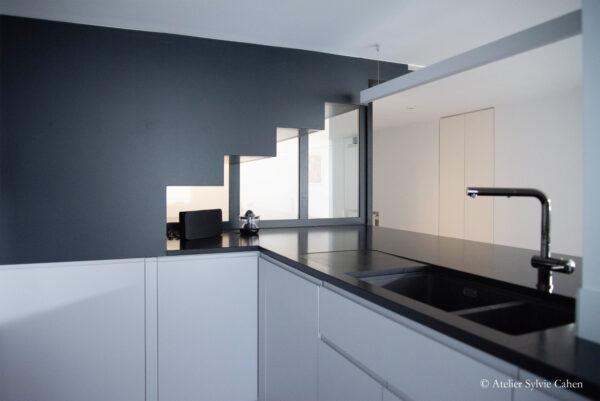 Loft à Lyon. Escalier (noir matte) montant à l'étage, partant du plan de travail (noir brillant) au fond de la cuisine.