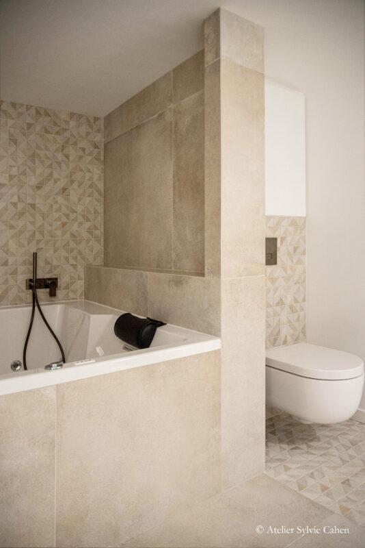 Loft à Lyon. Salle de bain avec baignoire et toilette suspendu, séparé par un mur en dalles de pierres et carrelage en mosaïque, dans les tons beiges.