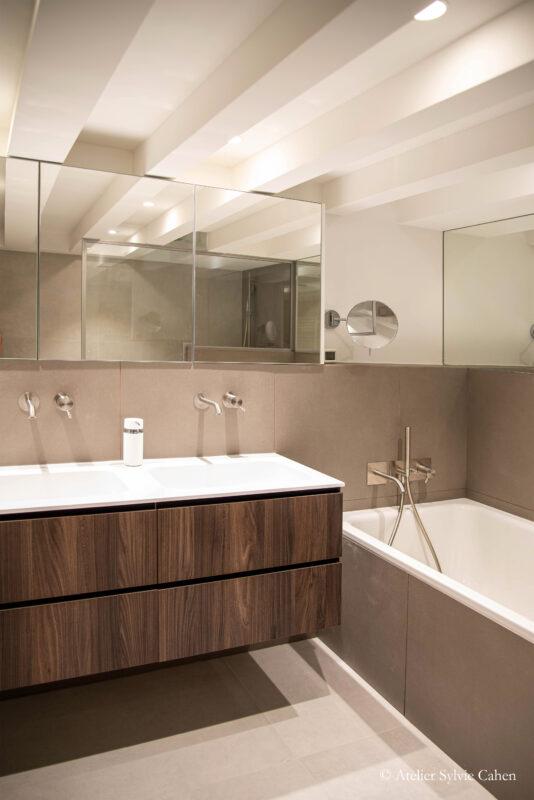 Loft à Lyon. Salle de bain avec baignoire, meuble en bois foncé, à double vasque, surmonté d'un meuble à deux portes miroirs.