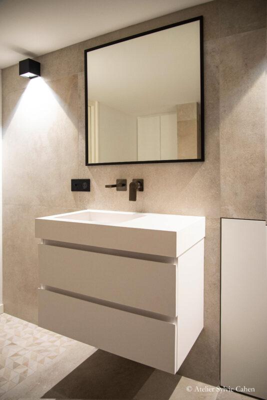 Loft à Lyon. Meuble à vasque encastrée, avec robinet encastré dans le mur, surmonté d'un miroir carré.