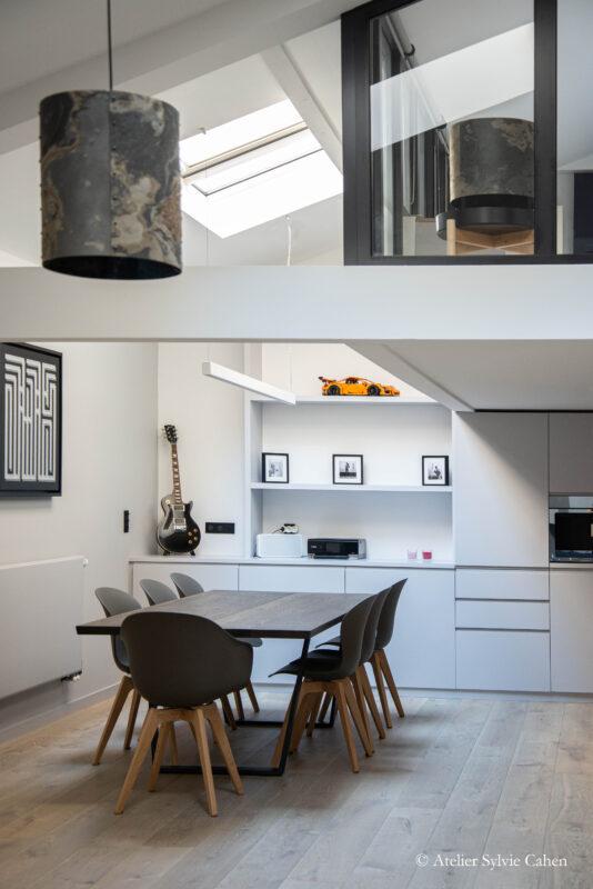 Loft à Lyon. Espace salle à manger avec table en bois et meuble de rangements blanc au fond de la pièce.