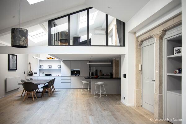 Loft à Lyon. Vue d'ensemble sur la grande pièce à vivre, avec espace salle à manger, espace cuisine avec bar et chambre en mezzanine.