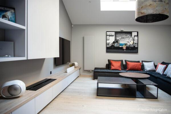 Loft à Lyon. Espace salon avec canapé d'angle, table basse asymétrique et meuble de rangement bas longeant le mur.