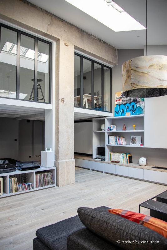 Loft à Lyon. Vue du canapé du salon, sur l'autre côté du meuble fait sur mesure, longeant l'autre coté du mur, et sur une autre partie de la mezzanine, avec deux verrières.