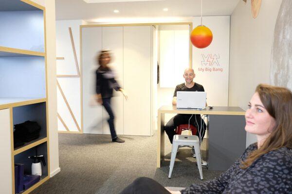 Studio ergonomique blanc et bois. Entrée du studio avec bureau d'accueil et coin attente.