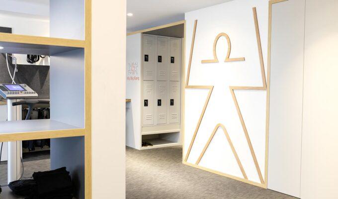 Studio ergonomique blanc et bois. Couloir donnant sur le mur avec le logo en plainte en bois et sur les casiers.