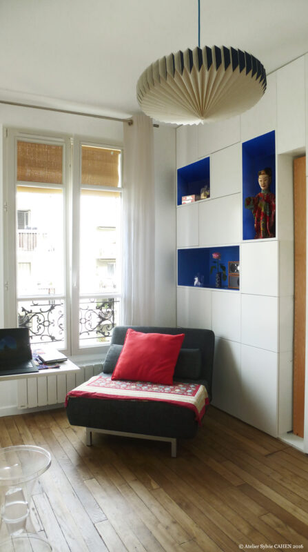 Appartement Origami. Une fois le paravent relevé et le lit replié la pièce est un salon avec un luminaire en pliage au plafond.