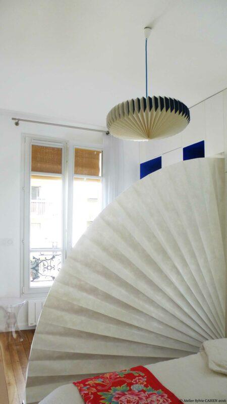 Appartement Origami. Un paravent en éventail permet d'isoler la chambre et un luminaire en pliage se trouve au plafond.