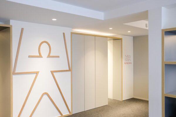 Studio ergonomique blanc et bois. Couloir avec murs composé du petit logo My Big Bang et du grand bonhomme en plaintes en bois.