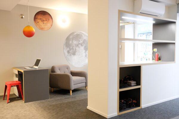 Studio ergonomique blanc et bois. Bureau d'accueil et coin attente vue de la salle de sport.