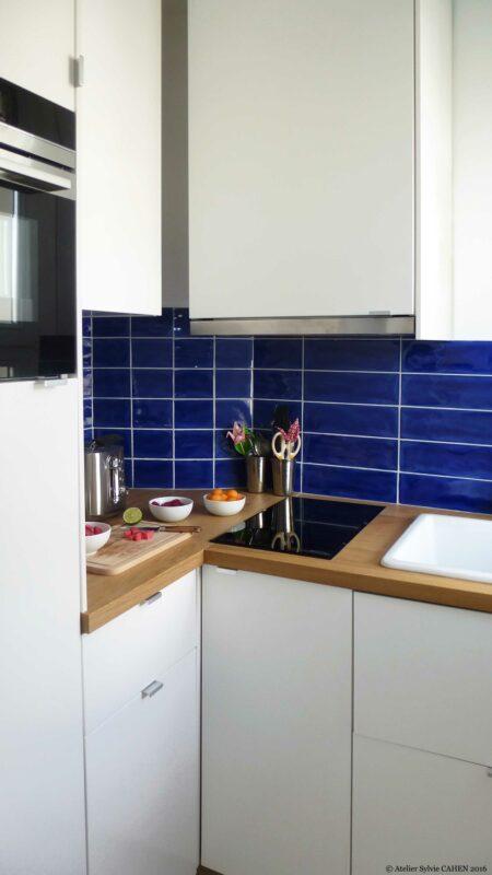 Appartement Origami. La cuisine a un carrelage mural bleu qui est le même que celui de la salle de bain.