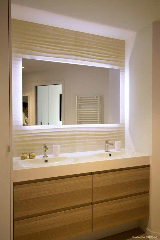 Le triplex parisien. Le carrelage minéral est associé au bois dans la salle d'eau parentale. Un grand miroir rétro-éclairé donne une ambiance très reposante à la salle d'eau.