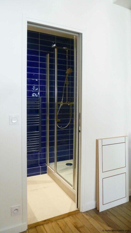 Appartement Origami. La salle de bain dispose d'une douche. Le carrelage mural est le même que celui de la cuisine.