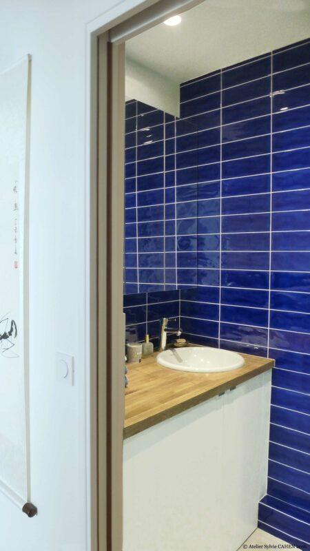 Appartement Origami. La salle de bain dispose d'un meuble sur mesure à vasque encastrée. Le carrelage mural est le même que celui de la cuisine.