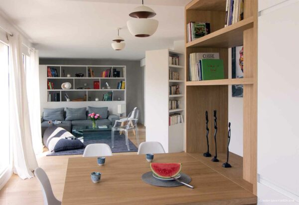 Le triplex parisien. La grande pièce à vivre ne présente aucune cloison. Les meubles structurants permettent de créer des vues et ainsi compartimenter l'espace : la bibliothèque de l'entrée sert également de meuble TV, la bibliothèque du fond dissimule un escalier pour descendre à l'espace parental. Les suspension Heres Comes The Sun de DCW Editions éclairent la cuisine et l'emplacement salle à manger.