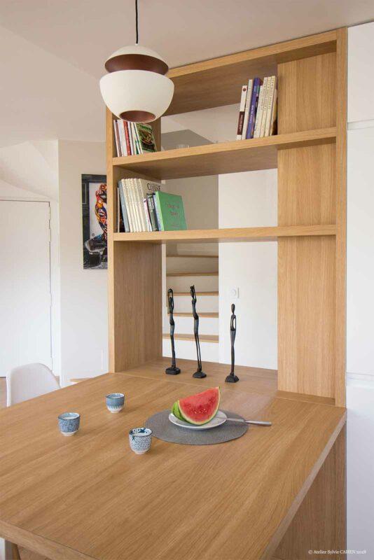 Le triplex parisien. La Table sur mesure en chêne vient dans la continuité de la bibliothèque traversante qui sert de moucharabié. L'ensemble du bois utilisé dans l'appartement est un chêne moyen. On aperçoit les escaliers qui sont habillés également de bois. Cela donne l'impression que le parquet de la même couleur s'envole vers l'étage.