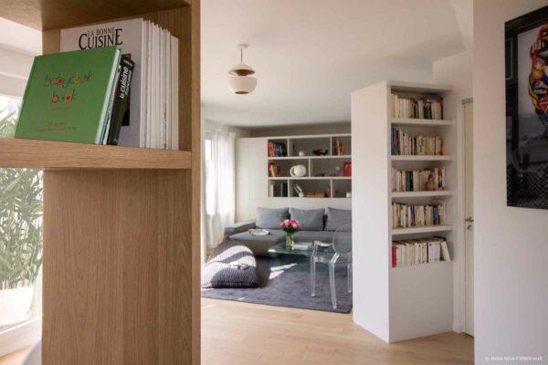 Le triplex parisien. Les meubles structurants qui compartimentent l'espace permettent de créer des vues. Ainsi, la bibliothèque de la cuisine permet de couper la vue vers l'espace sanitaires, la bibliothèque de l'entrée permet de couper la vue de l'entrée vers le séjour et la bibliothèque du fond derrière le canapé coupe la vue sur les escaliers menant à la chambre parentale se situant sous le séjour.