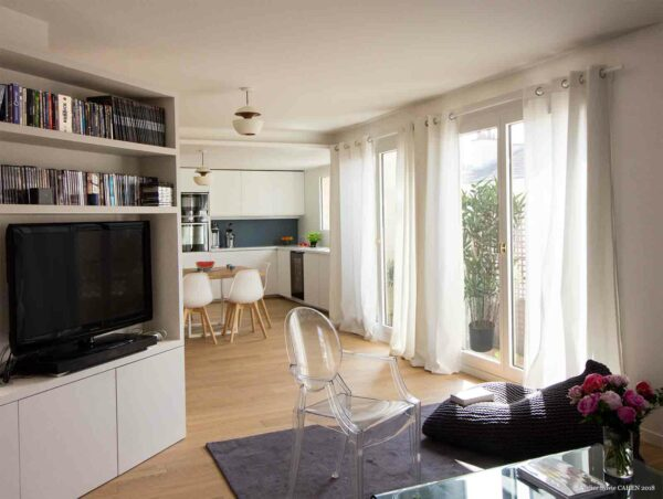 Le triplex parisien. Le séjour permet l'installation d'une grande télévision invisible depuis le reste du séjour. Celle-ci est dissimulée dans le meuble structure qui fait dos à l'entrée bibliothèque.