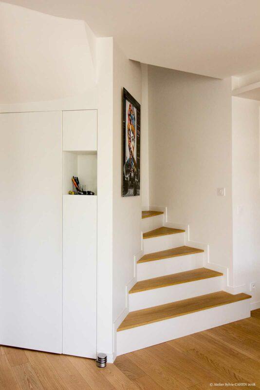 Le triplex parisien. Les escaliers existants ont été rénovés. La marche est pourvue d'une épaisseur de bois chêne massif identique au sol et les contremarches ont été peintes en blanc comme les murs. Cela donne l'impression que le parquet s'envole vers l'étage.
