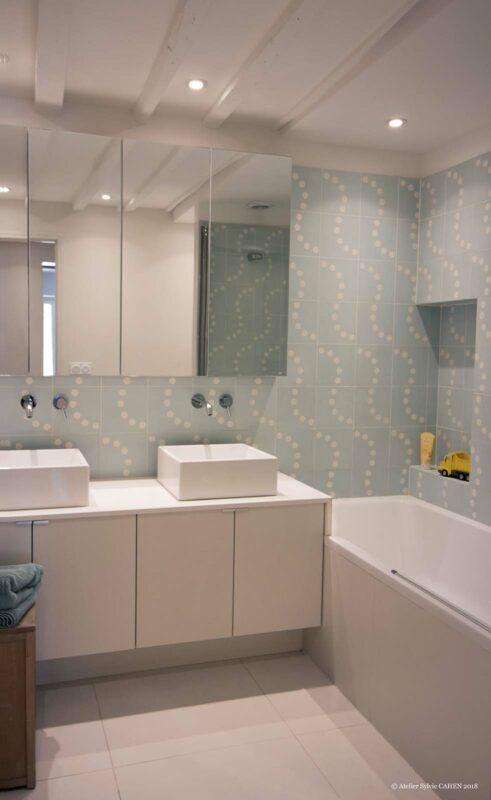 Appartement en structure bois. Salle de bain avec meuble à double vasque posée, baignoire et meuble 4 portes, à miroirs.
