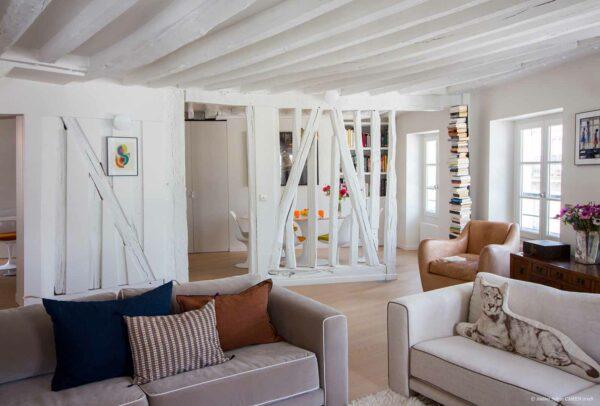 Appartement en structure bois. Salon / Séjour, avec cloison ouvertes sur une structure en bois avec les poutres peintes en blanc.