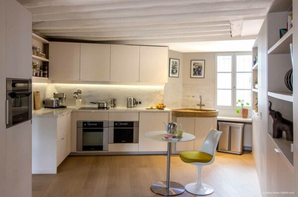 Appartement en structure bois. Cuisine ouverte avec évier en pierre et petite table d'appoint.