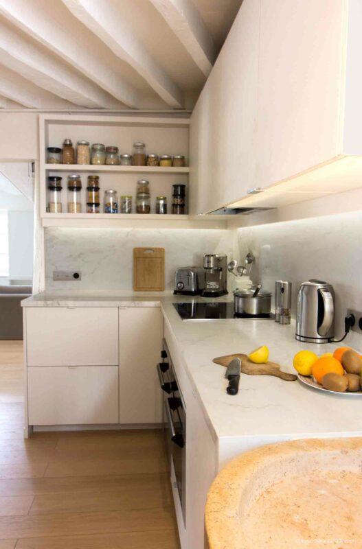 Appartement en structure bois. Cuisine ouverte à meuble blanc et plan de travail en marbre.