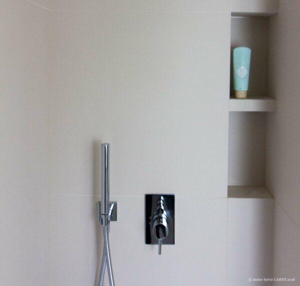 Appartement en structure bois. Dans la salle de bain, le robinet et le mitigeur de la douche sont en acier, de forme moderne.