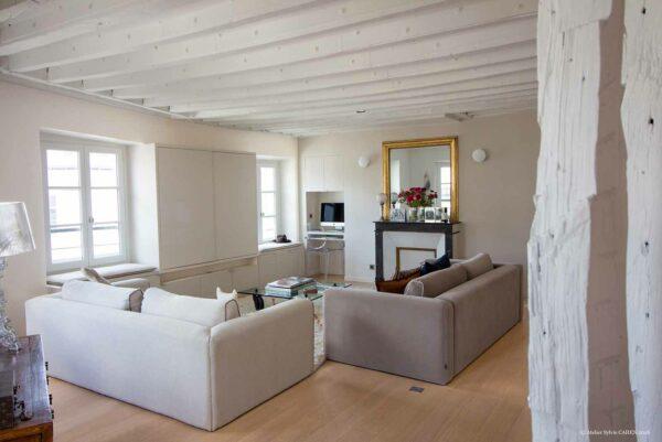 Appartement en structure bois. Salon / Séjour avec bureau encastré dans le mur et poutres peintes en blanc.