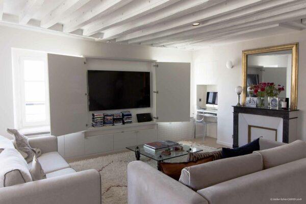 Appartement en structure bois. Salon / Séjour avec bureau encastré dans le mur, meuble télévision sur mesure, et poutres peintes en blanc.