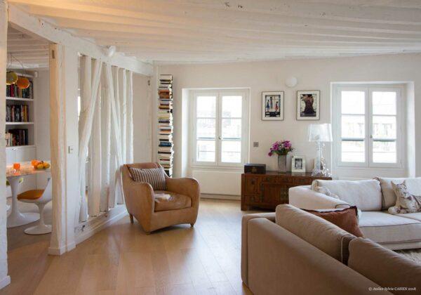 Appartement en structure bois. Ouverture du Salon / Séjour sur la salle à manger. Les cloison ont été ouvertes sur une structure en bois avec les poutres peintes en blanc.