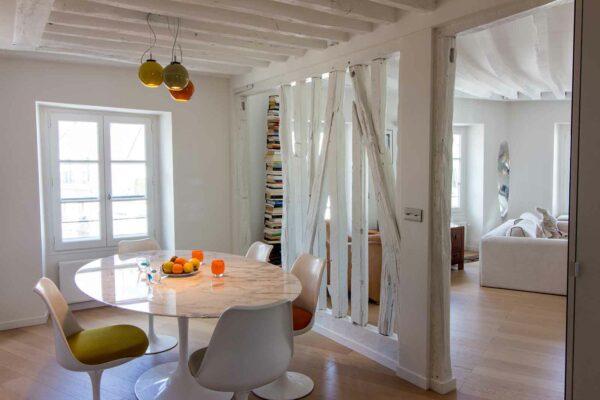 Appartement en structure bois. Ouverture de la salle à manger sur le Salon / Séjour. Les cloison ont été ouvertes sur une structure en bois avec les poutres peintes en blanc.
