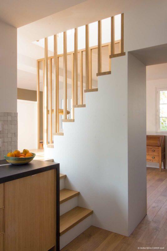 Appartement lumineux et boisé. L'escalier central est semi-ouvert par un barreaudage en chêne.