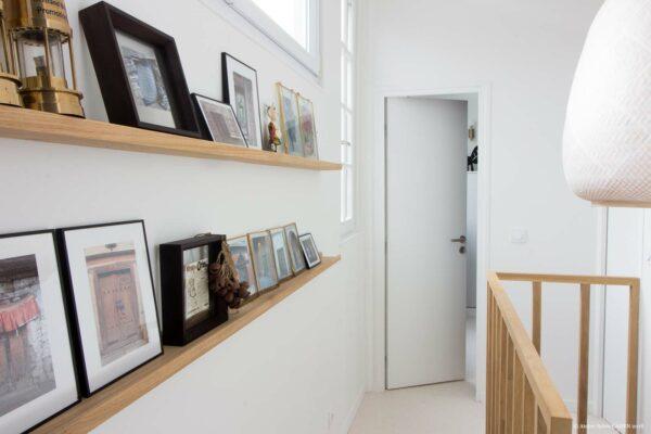 Appartement lumineux et boisé. Le couloir de l'étage donne sur la chambre. Son mur gauche est aménagé avec des étagères en bois sur mesures. On aperçoit le garde corps chêne menant à l'escalier.