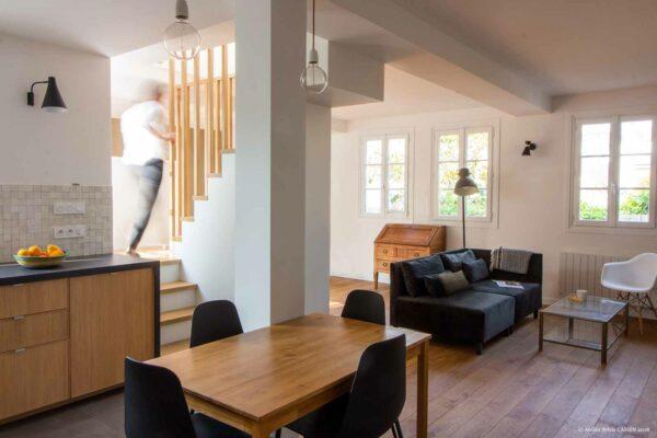 Appartement lumineux et boisé. La Pièce principale est vue de la cuisine. On peut voir l'espace salon, la table de la cuisine et le bas de l'escalier central.